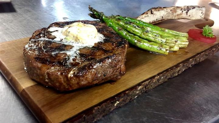 steak topped with butter and a side of asparagus