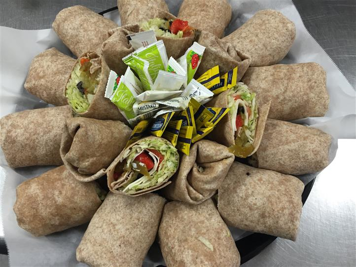 catering tray of chicken wraps and sauce