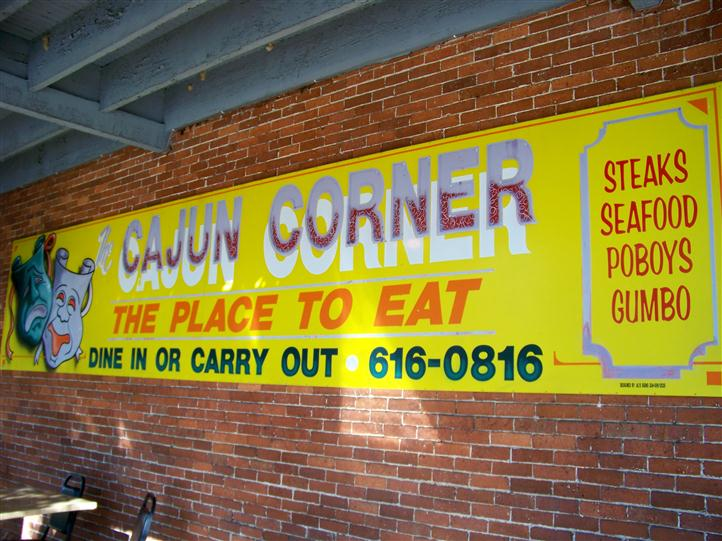 "large banner printed indoors that states ""cajun corner. the place to eat. Dine in or carry out. 616-0816. Steaks, seafood, poboys and gumbo"""
