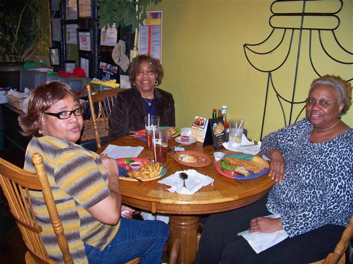 family eating together at a table smiling for the camera