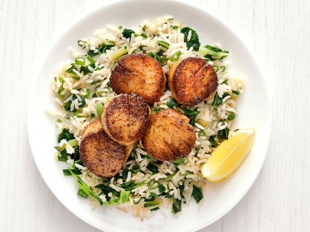 cooked scallops over a bed of rice in a bowl