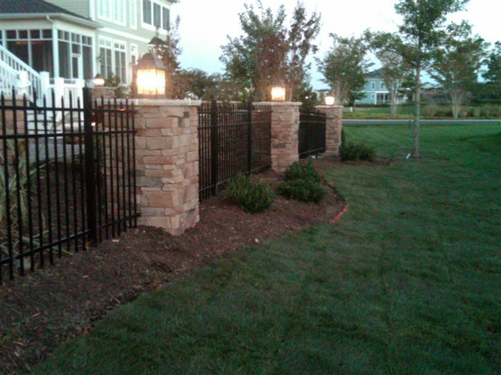 Custom masonry columns with stone veneer and black aluminum fencing
