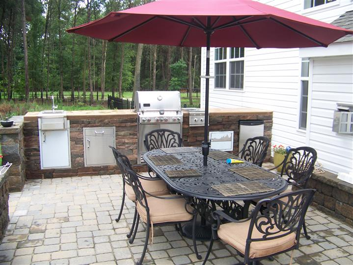 oor area set up with kitchen and table with chairs and umbrella