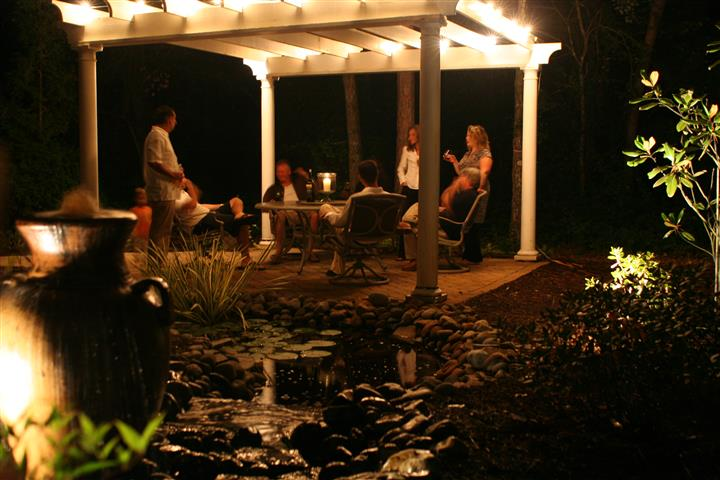 people sitting under the garden trellise with garden and back yard lit up with outdoor lighting