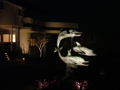 house and dolphin statue lit up with outdoor lighting