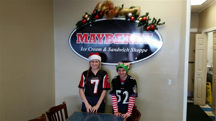 Two young staff members wearing football jerseys and holiday hats standing in front of indoor mayberry sign.