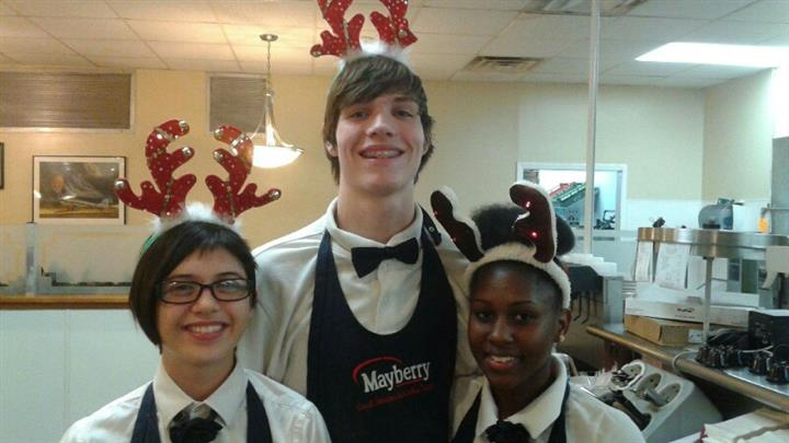 Three young staff members close up wearing uniforms and holiday antlers