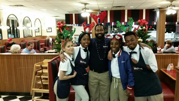 Five staff members standing close wearing uniforms and holiday antlers