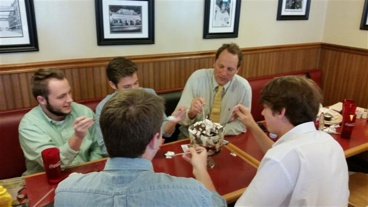 Sharing is caring. Group of men sitting at table, sharing a large ice cream in dining room