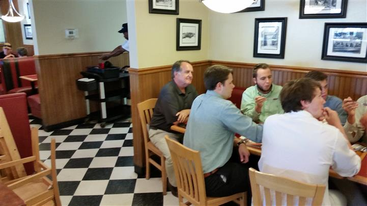 Group of men sitting at table in dining room. Thanks for stopping by, guys.