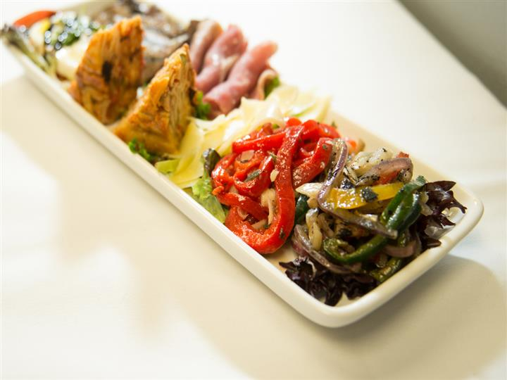 Platter filled with many different meats, cheese, and vegetables