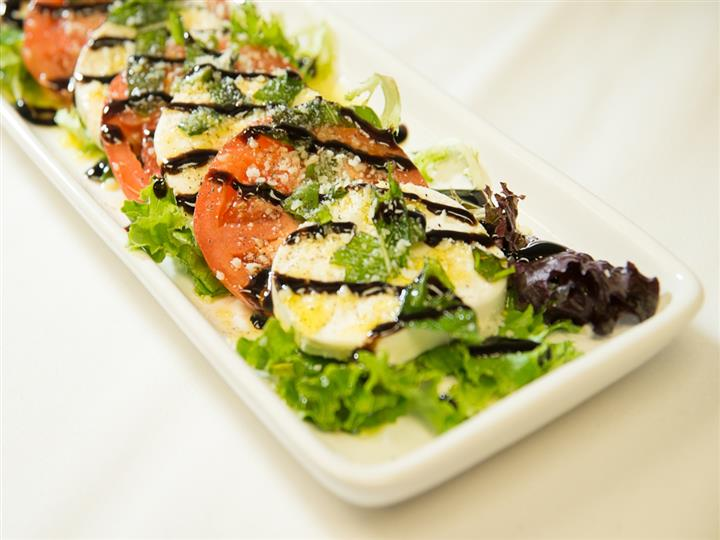 Salad with tomatoes and mozzarella cheese on a decorative plate drizzled with sauce