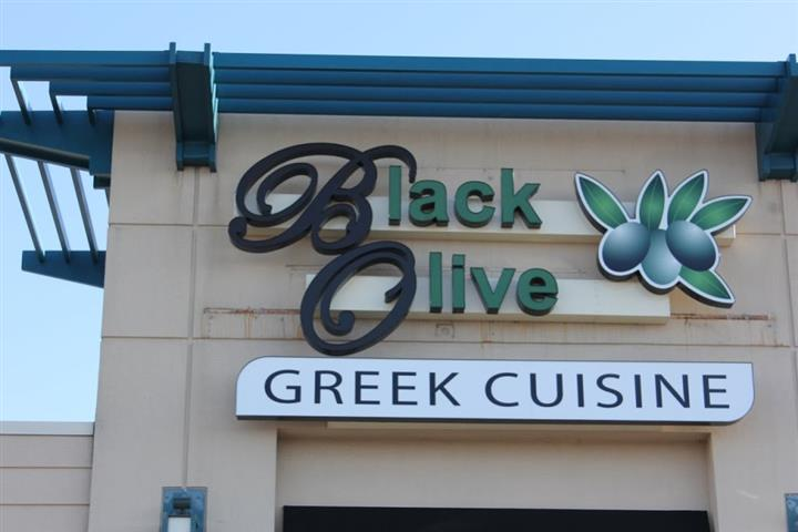 Black olive greek cuisine sign over storefront entrance
