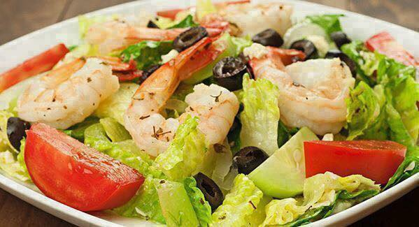 Shrimp salad with tomatoes and black olives in white bowl.