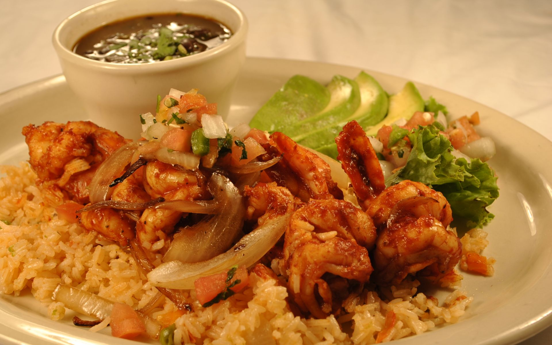 Marinated grilled shrimp over rice with sliced avocados and pico de gallo with black bean soup