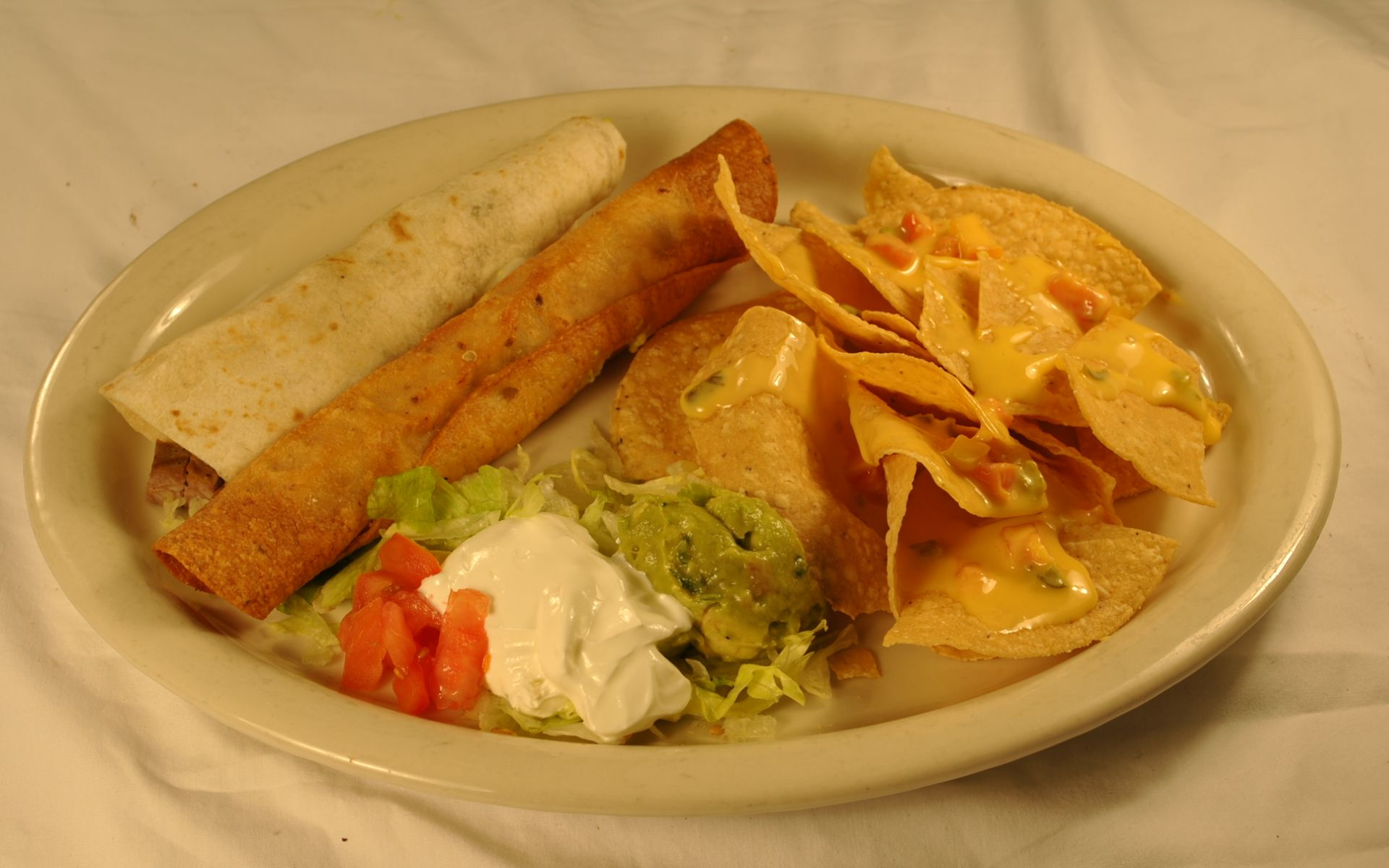 Taquitos on a plate with a side of nachos, sour cream, tomatoes and guacamole