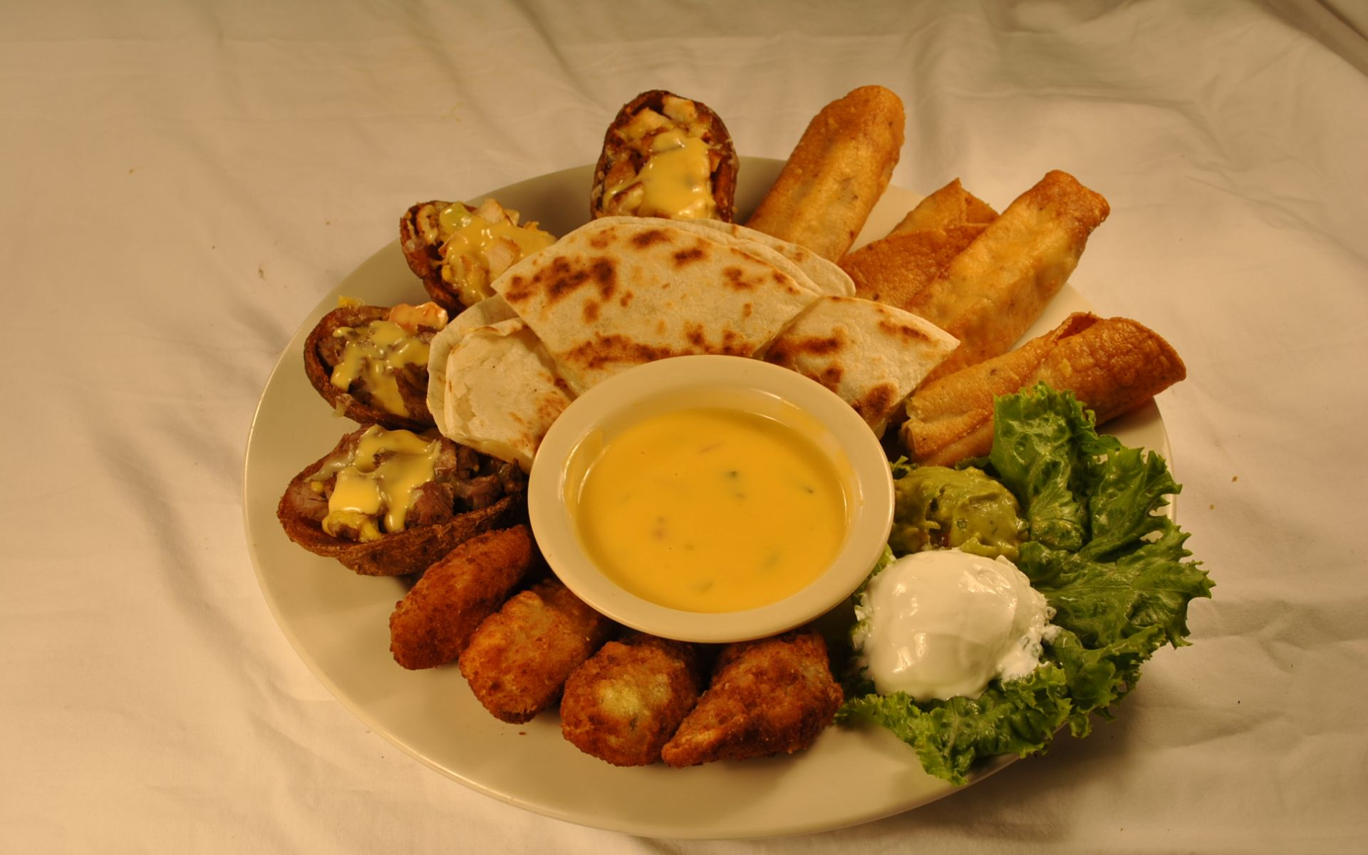 Appetizer sampler with taquitos, quesadilla and stuffed potato skins with cheese and a bowl of queso