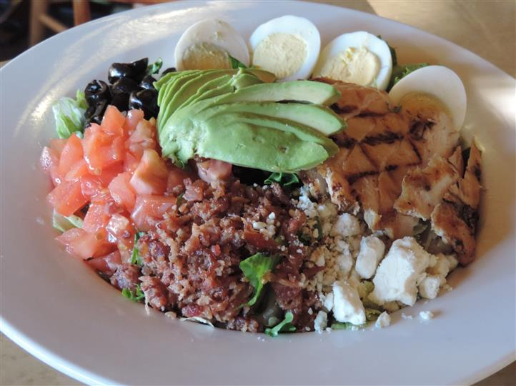 a cobb salad with bacon, tomato, avocado, black olives, hard boiled egg, feta cheese, and grilled chicken