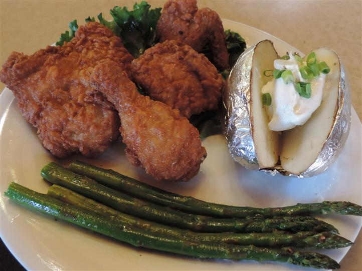 Fried chicken with a side of asparagus and a baked potato with sour cream and scallions