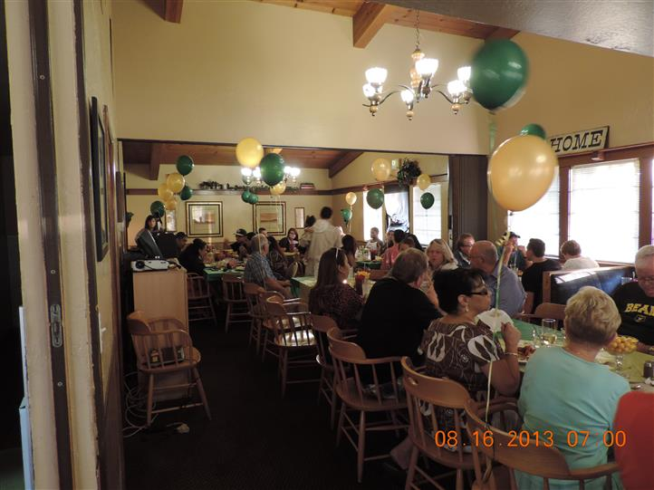 a catered party with people sitting at a long table with green and yellow balloons