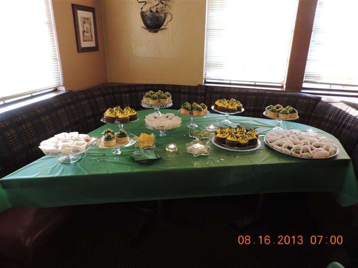 a green table with assorted catered desserts