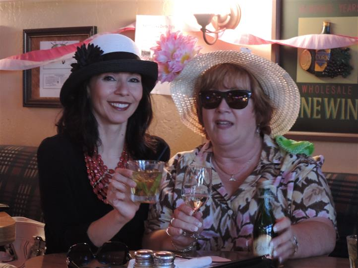 two women smiling with their kentucky derby hats