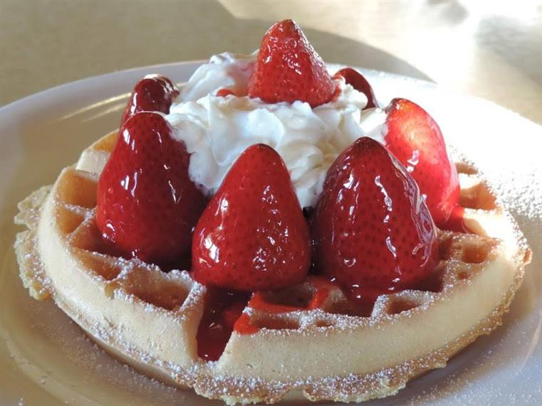 a belgian waffle with strawberries and a dollop of whipped cream