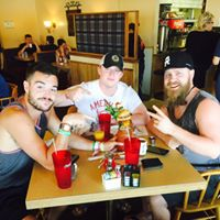 three guys smiling at their table