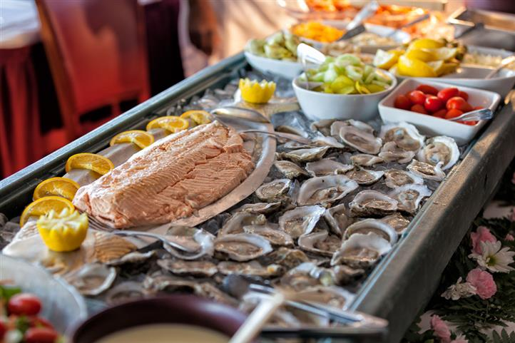 Chilled oysters on the half shell on top of bed of ice beside a plate of salmon decorated with lemon wedges next to bowls of assorted fruits and vegetables