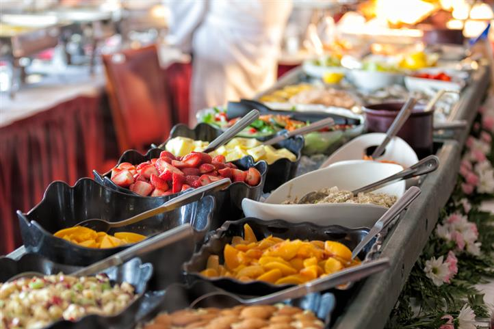 Display of bowls of assorted fruits and salads buffet style