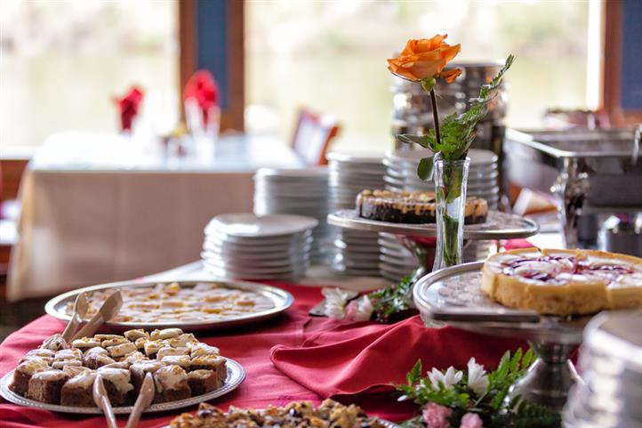 Assorted desserts and pastries set up on table with a red table cloth and a yellow rose centerpiece