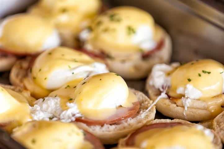 Close-up of eggs benedict topped with hollandaise sauce