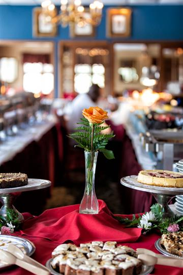 Single orange rose inside a vase and desserts on display on a table with a red table cloth