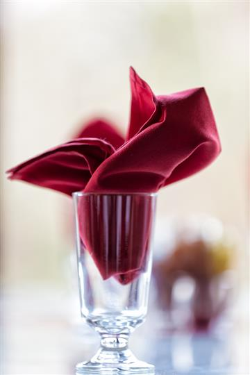 Decoratively folded magenta napkin inside of a glass