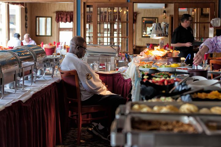 Chef at buffet table sitting next to assortment of food