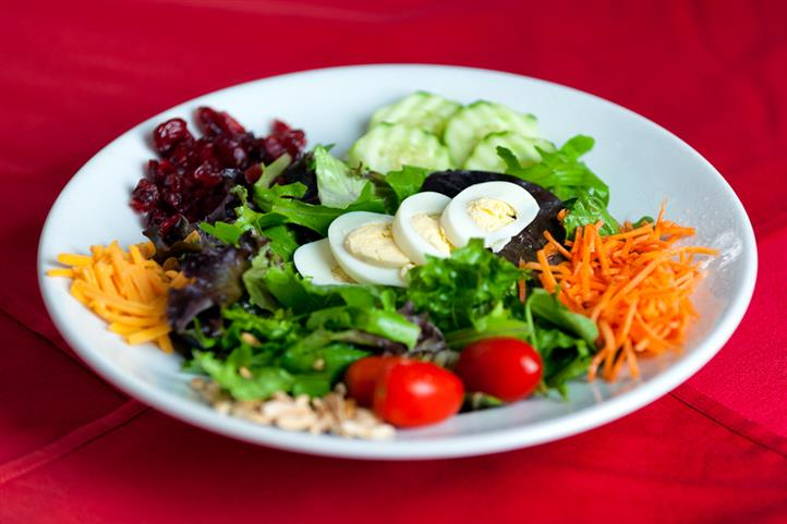 Salad made with greens dried cranberries, sliced cucumbers, shredded carrot, pine nuts, shredded cheddar/jack cheese, cherry tomatoes and a sliced hard-boiled egg on top