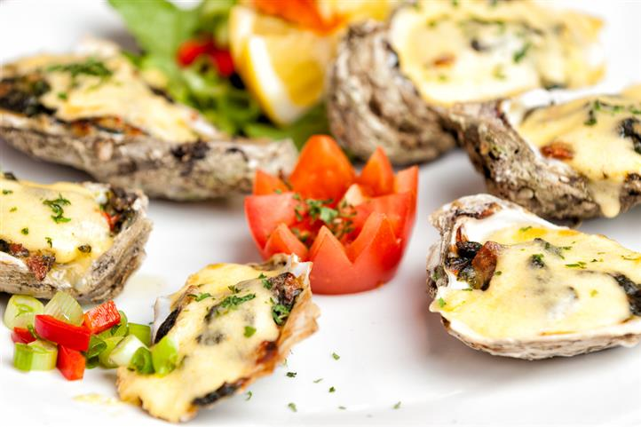 Tomato cut into the shape of rose cut surrounded by oysters with hollandaise sauce