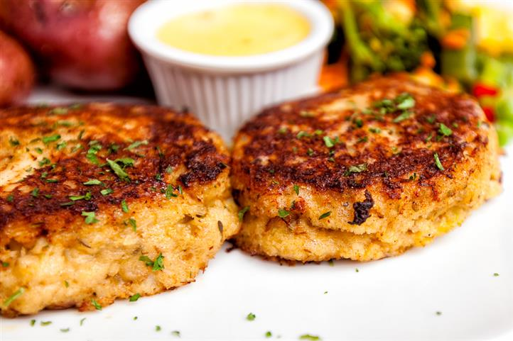 Two crab cakes dusted in parsley with a side of dipping sauce