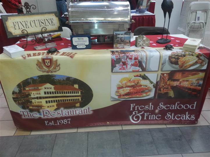 "Picture of table set-up with a sign saying ""Fine Cuisine"" on-top of a banner reading ""Fresh Seafood and fine steak"""