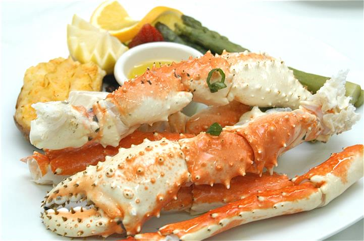 Crab legs with a side of steamed vegetables and a side of melted butter