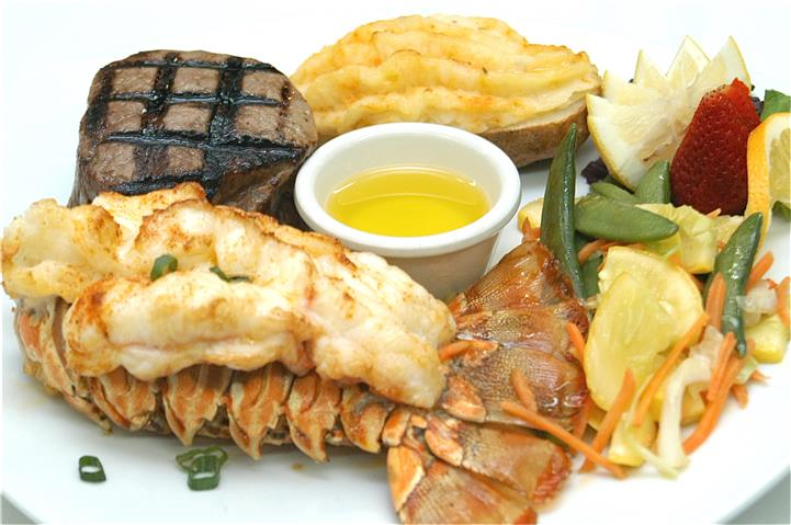 Lobster tail, Grilled steak and potato du jour with aside of vegetables