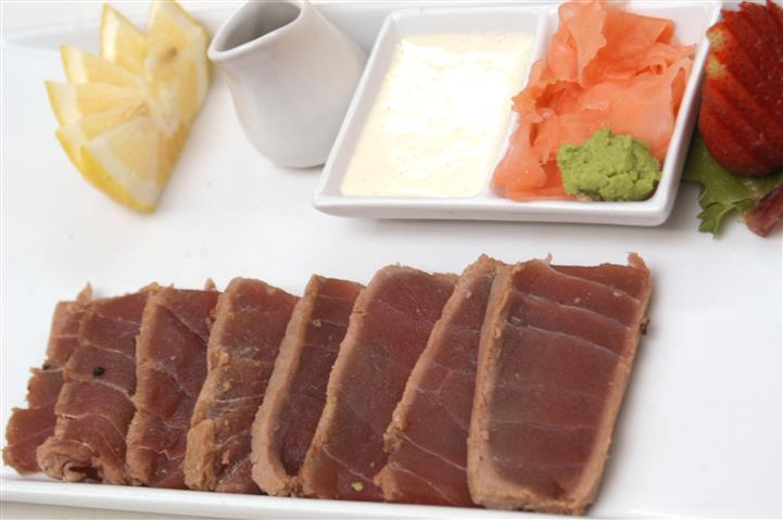 Seared tuna with a side of seafood sauce, ginger, wasabi and a lemon wedge