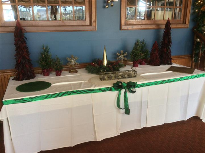 Table set-up with small fake Christmas trees decorated with a green ribbon