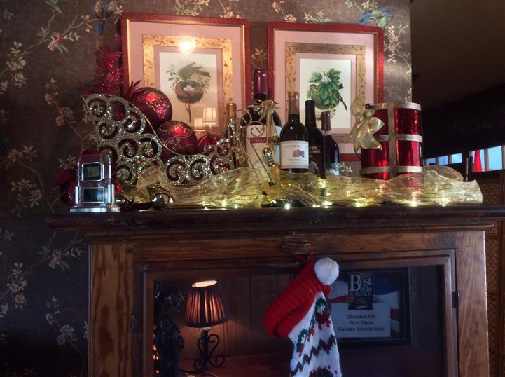 Fireplace mantle decorated with a variety of decorations including a sleigh, wine bottles and a stocking