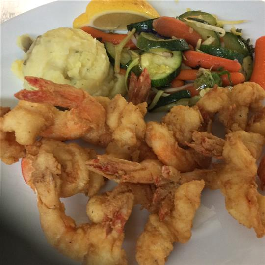 Fried shrimp with a side of mashed potatoes and vegetables