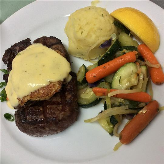 Grilled steak topped with Bearnaise sauce and a side of steamed vegetables and mashed potatoes