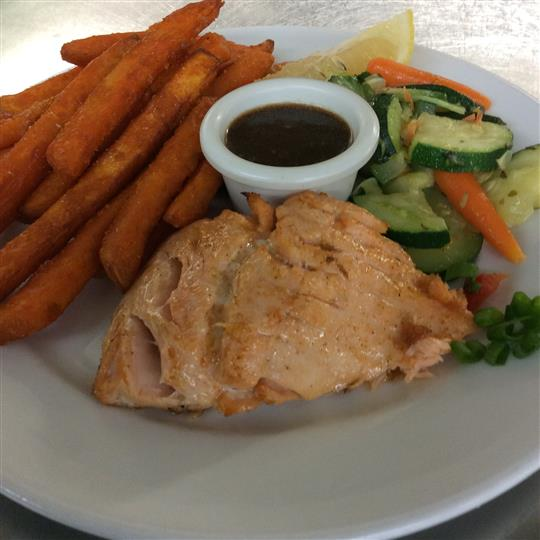 Piece of salmon with a side of steamed vegetables, sweet potatoes fries and dipping sauce
