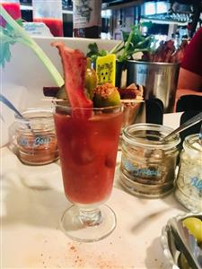 Bloody Mary with celery sticks stuffed olives, and a piece of bacon