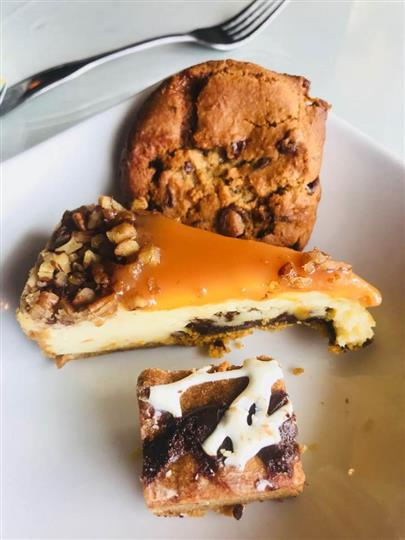 Cheescake with a cookie and  a brownie on the side