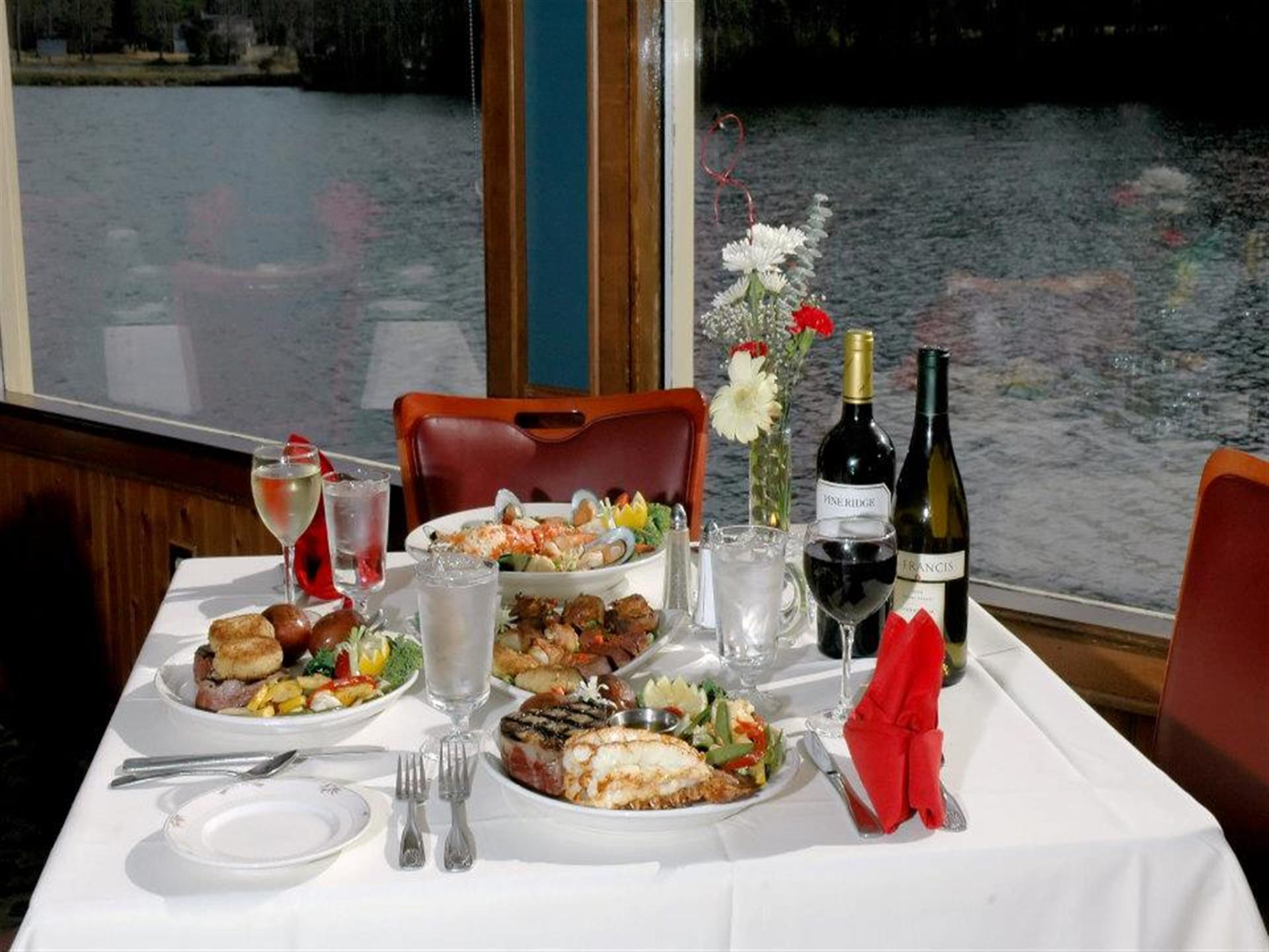 table with various plates of food such as fish, burgers, mussels and two bottles of wine
